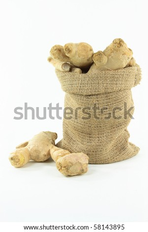 Still picture of Ginger roots in burlap bag over white background. - stock photo