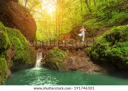 Still, relaxation, Woman practices yoga at the waterfall  - stock photo