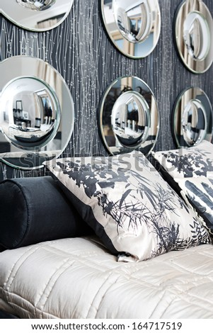 Still view of an elegant home luxury bedroom tastefully decorated in two colors, black and white beige, with aligned round mirrors and shiny silk fabrics and organic cushions. Interior with no people. - stock photo