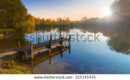 Still waters reflect the wooden piers Lake at Sunset - stock photo