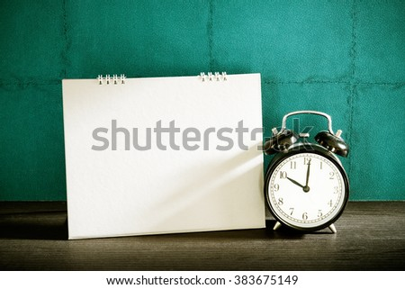 Stillife of desk calendar with alarm clock on wood table. Vintage filtered. - stock photo