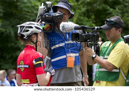 STILLWATER, MINNESOTA - JUNE 17: Television reporters interview pro cyclist Megan Guarnier following her Stillwater Criterium win at 2012 Nature Valley Grand Prix on June 17, 2012 in Stillwater.