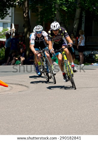 STILLWATER, MN -  JUNE 21: Cyclist Kevin Girkins leads race as Ben Hill closes in at stage six of prestigious North Star Grand Prix pro cycling event on June 21, 2015 in Stillwater, Minnesota.  - stock photo