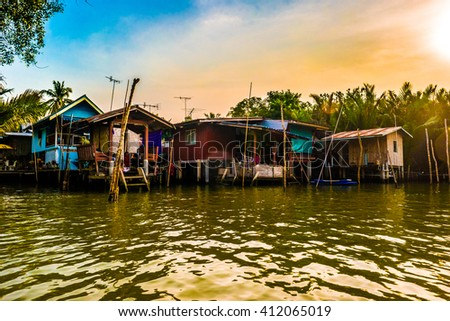 Stilt houses built above river Mae Klong in Amphawa, rural Thailand. Beautiful countryside landscape at sunset. - stock photo