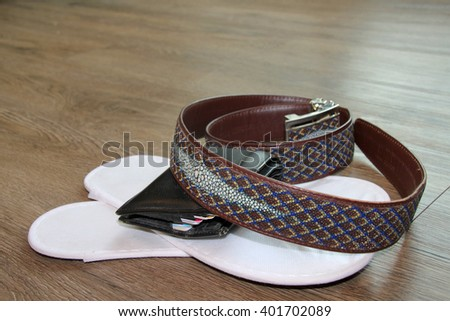 stingray skin belt and white sandals and money purse on wooden floor in the morning light room