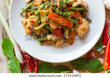 stir fish with spicy curry on wood table