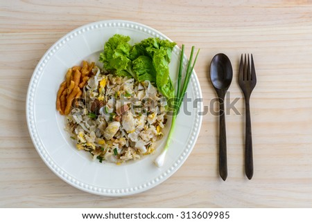 Stir fried Chicken with Noodles, egg and vegetable on wooden table - stock photo