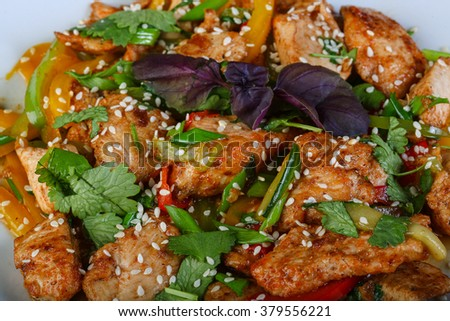 Stir-fried chicken with vegetables and herbs - stock photo