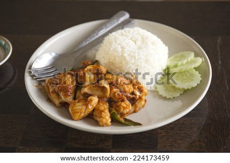Stir fried Curry Squid with Steam rice on the plate - stock photo