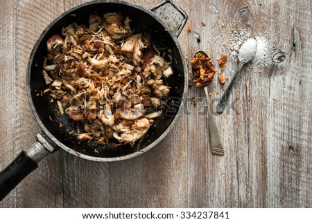 stir-fried meat in pan on wooden table with spices - stock photo