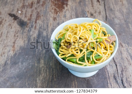 Stir-Fried noodles with pork and vegetables on grungy wooden table