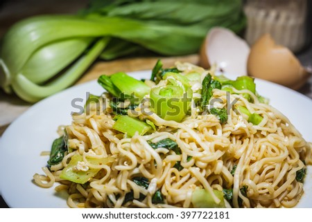 Stir fried noodles with vegetables in brown plate and on wood board