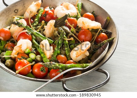 Stir-fried of Shrimps, green asparagus, capers, spring onion and peppermint in old pan
