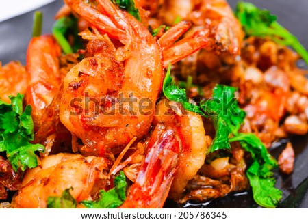 Stir fried shrimp with peppers and garlic on rectangle black plates