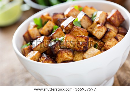 Stir fried tofu in a bowl with sesame and greens