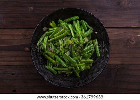 Stir fry green beans on black bowl on brown wooden background - stock photo