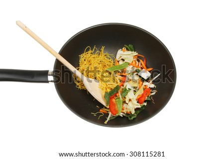 Stir fry ingredients with a wooden spoon in a wok isolated against white