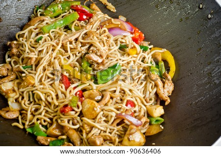 Stir fry noodle with chicken in a wok pan