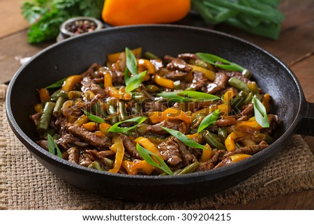 Stir frying beef with sweet peppers and green beans - stock photo