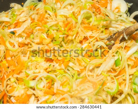 Stir frying shredded vegetables in large pan - stock photo