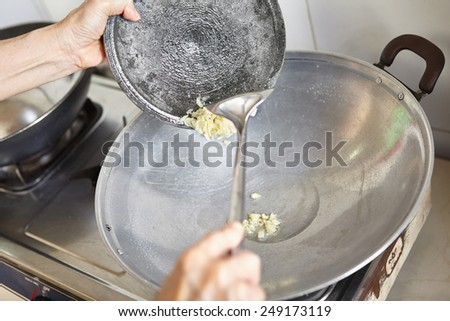 Stir frying the crushed garlic on the wok - stock photo