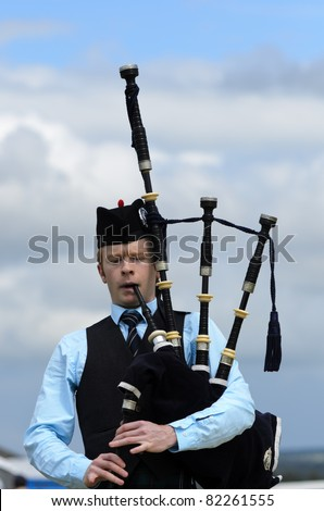 STIRLING, SCOTLAND - JULY 10: Piper competing in solo piping competition during Stirling Highland Games on July 10, 2011 in Stirling, Scotland - stock photo