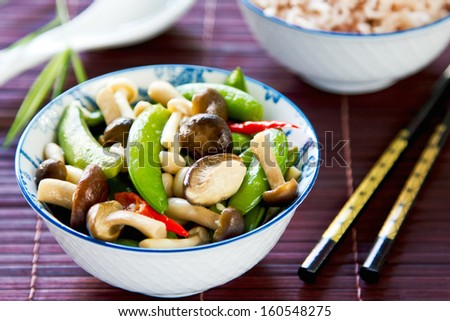 Stirred fried snap pea with mushroom in oyster sauce by brown rice - stock photo