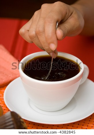 Stirring black coffee in a white cup and saucer - stock photo