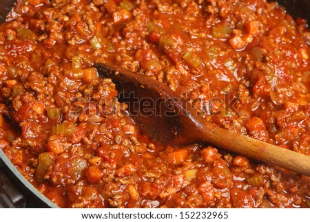 Stirring Spaghetti Bolognese with wooden spoon - stock photo