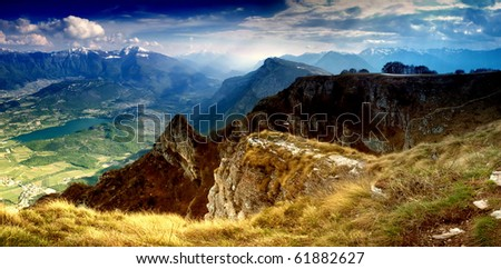 Stitched Panorama in dolomites mountains, A beautiful landscape view with sun beams through clouds from the top of a mountain. - stock photo