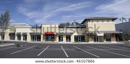stitched panoramic of an upscale storefront mall with tin roof and colorful awnings - stock photo