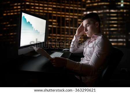 Stock analytic and broker looking at stock charts going down after sales report - stock photo