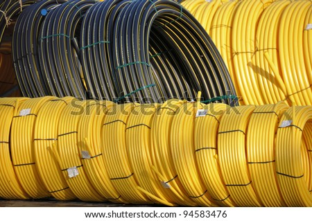 Stock black and yellow coiled plastic pipes - stock photo