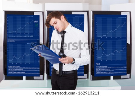 Stock Broker Using Telephone Sitting In Front Of Desktop