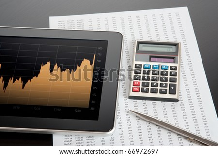 Stock business and market analyze with digital tablet, calculator, pen and printed data sheet