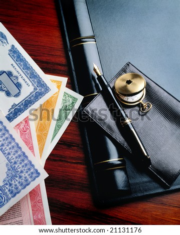 Stock certificates on desk with wallet and pen - stock photo