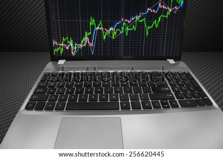 Stock chart on laptop computer monitor screen. Share price quotes of green and blue growth up trend on display over dark background. Modern technology internet live bank transfer of online data. - stock photo