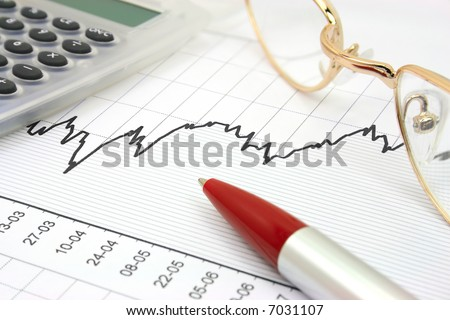 Stock chart with calculator, red pen and eyeglasses - stock photo