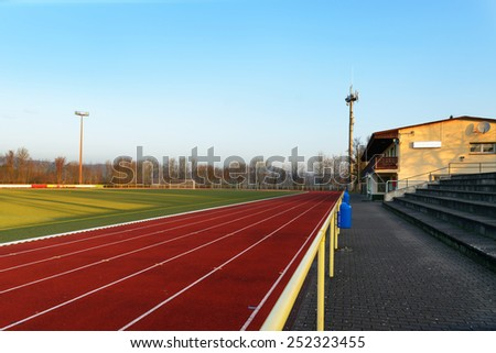 Stock image of a football field with running track and clubhouse in the evening, signifying concept of dreams and aspirations - stock photo