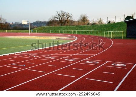 Stock image of a football field with running track and clubhouse in the evening, signifying concept of dreams and aspirations