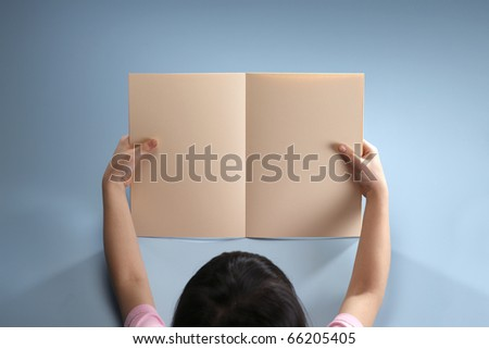 Stock image of a girl holding a blank book. - stock photo