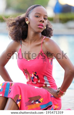 Stock image of a Jamaican woman sitting with hands on her hips - stock photo