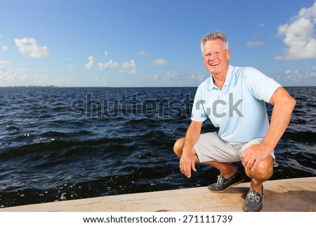 Stock image of a man squatting by the seawall to the ocean - stock photo