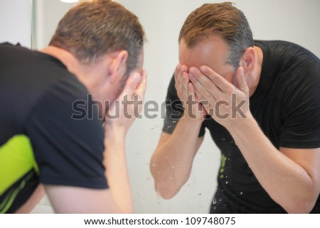 Stock image of a man washing his face in the mirror - stock photo