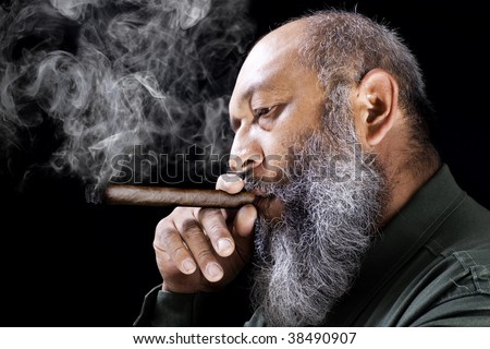 Stock image of adult male with long beard smoking cigar over dark background