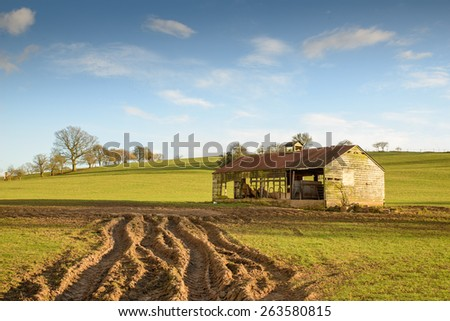 Stock image of an old barn in a meadow with blue sky and clouds - stock photo