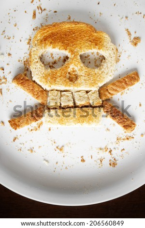 Stock image of bread skull and crossbones on white plate - stock photo