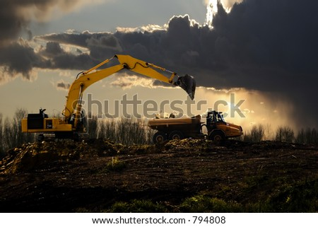 Stock image of earth mover trying to get a last load before the storm - stock photo