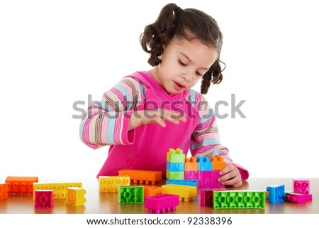 Stock image of little girl playing with construction blocks over white background - stock photo
