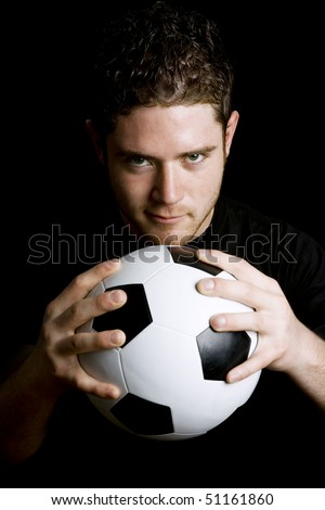 Stock image of man holding soccer ball over dark background